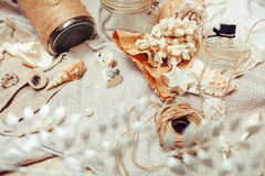 A lot of sea theme in mess like shells, candles, perfume, girl stuff on linen, pretty textured post card view vintage Royalty Free Stock Photography