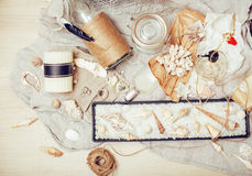 A lot of sea theme in mess like shells, candles, perfume, girl stuff on linen, pretty textured post card view vintage Stock Photography