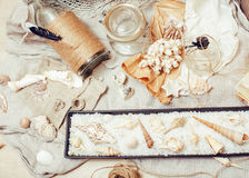 A lot of sea theme in mess like shells, candles, perfume, girl stuff on linen, pretty textured post card view vintage Stock Images