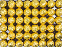 A lot of shiny golden chocolate wrapper in line on white background.. A lot of shiny golden chocolate wrapper in line on white background Stock Photography
