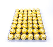 A lot of shiny golden chocolate wrapper in line on white background.. A lot of shiny golden chocolate wrapper in line on white background Royalty Free Stock Images
