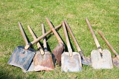 A lot of shovels, household equipment for cleaning, arrangement of territory, digging of the earth lie on the green. Grass royalty free stock photo