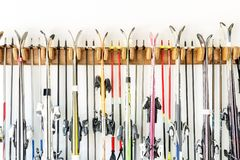 Lot of ski hanged on customized wooden wall mount at garage for seasonal storage. Extreme winter sport equipment handling at home. Warehouse royalty free stock photos