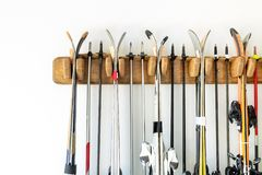 Lot of ski hanged on customized wooden wall mount at garage for seasonal storage. Extreme winter sport equipment handling at home. Warehouse stock photos