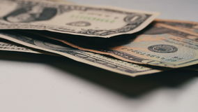 Lot of small dollar bills fall on the table with a white background macro close up stock footage