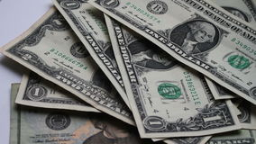 Lot of small dollar bills swaying in the wind on the table with a white background macro close up stock footage