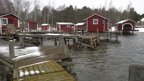A lot of small fish houses for fishing gear and boats on Baltic sea in winter. Dolly. stock video