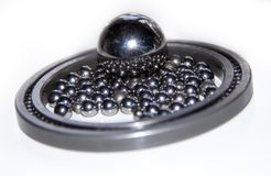 A lot of small stainless balls mirroring in one big stainless ball within a slim ball bearing. With selective focus Royalty Free Stock Photo