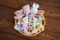 A lot of small toys in a wooden bowl, bears, bunnies, elephant, cat, fish. Toys for photo shoots of newborns Stock Image