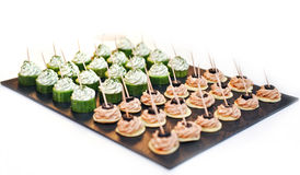 A lot of snacks with pate and black olives on black near four rows of cucumber with cream cheese Stock Image