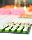 A lot of snacks with pate and black olives on black tray near four rows of cucumber with cream cheese Royalty Free Stock Image