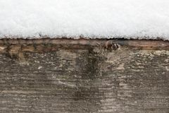A lot of snow lying on a wooden beam, beautiful abstract winter background.  Royalty Free Stock Photo