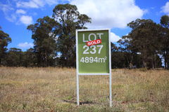 Lot sold. Sign-board with LOT for sale on an Australian countryside building ground - already sold stock image