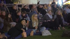 A lot of spectators in the movie theater outdoors in the evening.