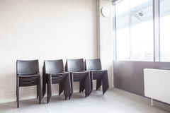 Lot of stacked chairs. Next to the window in the room, there are stacked chairs Royalty Free Stock Photo