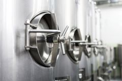 A lot of stainless steel tanks with large round hatches, modern beverage production. Food industry Royalty Free Stock Photography