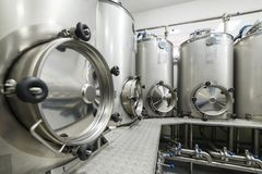 A lot of stainless steel tanks with large round hatches, modern beverage production. Food industry Stock Image