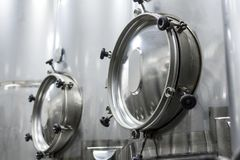 A lot of stainless steel tanks with large round hatches, modern beverage production. Food industry Stock Photo