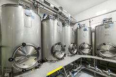 A lot of stainless steel tanks with large round hatches, modern beverage production. Royalty Free Stock Image