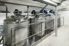 A lot of stainless steel tanks with large round hatches, modern beverage production. Stock Photo