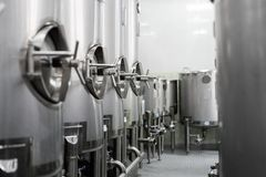 A lot of stainless steel tanks with large round hatches, modern beverage production. Royalty Free Stock Photography