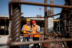 A lot of steel frames. Architect and structural engineer in orange work vests and helmets discuss a building project on stock image