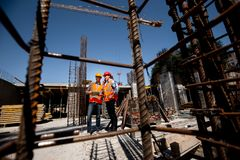 A lot of steel frames. Architect and structural engineer in orange work vests and helmets discuss a building project on royalty free stock photos
