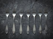 A lot of steel spoons on a black concrete table. Top view. Kitchen cutlery.  royalty free stock photography