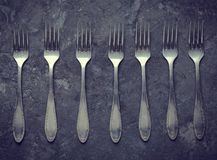A lot of steel spoons on a black concrete table. Top view. Kitchen cutlery royalty free stock image