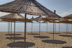 A lot of straw beach umbrellas on the beach, casting a shadow stock images