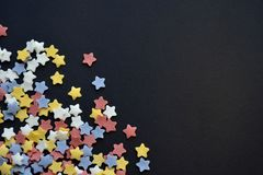 A lot of sugar colored stars on corner of black background macro, background for confectioners with a copyspace stock photos