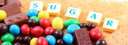 A lot of sweets, brown sugar and word sugar, unhealthy food Stock Photos