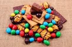 A lot of sweets on jute burlap, unhealthy food Royalty Free Stock Photos