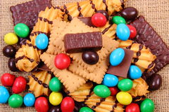 A lot of sweets on jute burlap, unhealthy food. Heap of candies and cookies on jute burlap, too many sweets, concept of unhealthy food and reduction of eating royalty free stock images