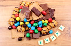 A lot of sweets with word sugar on wooden surface, unhealthy food Royalty Free Stock Photo