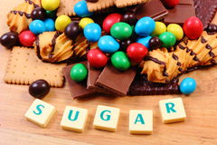 A lot of sweets with word sugar on wooden surface, unhealthy food Stock Photo