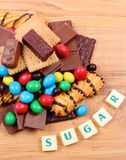 A lot of sweets with word sugar on wooden surface, unhealthy food Stock Image