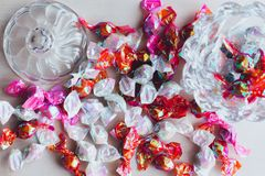 A lot of tasty and sweet candy in a bright wrap lie on a light surface. Several candies are in a candy glass bowl royalty free stock images