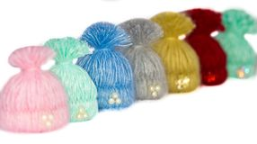Seven beautiful multi-colored caps - handmade brooches lined up. A lot of them like invisible athletes - children stand in a row. And only these gorgeous Royalty Free Stock Images
