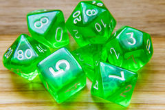 A lot of translucent green playing dice on a wooden background w Stock Photos