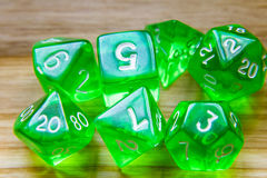 A lot of translucent green playing dice on a wooden background w Royalty Free Stock Photography
