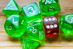 A lot of translucent green playing dice on a wooden background w Royalty Free Stock Images