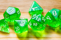 A lot of translucent green playing dice on a wooden background w Royalty Free Stock Image