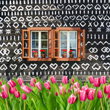 A lot of tulips in front of painted wooden summer cottage Royalty Free Stock Photos