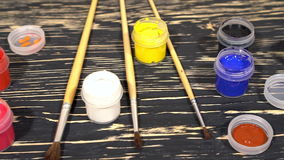 A lot of varicolored paint gouache jars with brushes on wooden background stock video