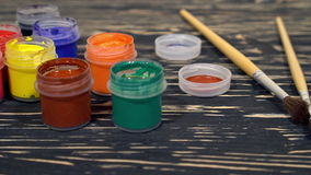 A lot of varicolored paint gouache jars with brushes on wooden background stock video footage