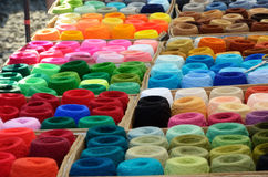 A lot of varicolored spools of thread outdoor. Many bobbins of motley acrylic textile fibers are gathered together Stock Image