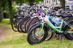 A lot of various bicycles on a grass. In a town Stock Photos