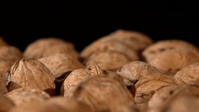 A lot of walnuts, on black, rotation, close up stock footage