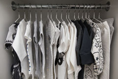A lot of white children`s clothes on hangers. Children`s wardrobe with clothes.  Royalty Free Stock Photo
